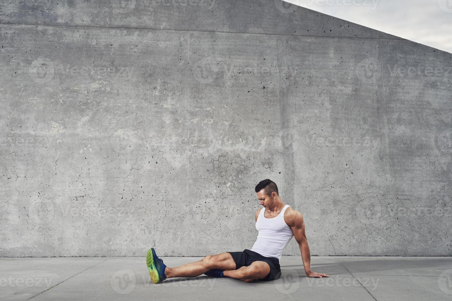 Fitness athlete man relaxing and stretching muscles and legs photo