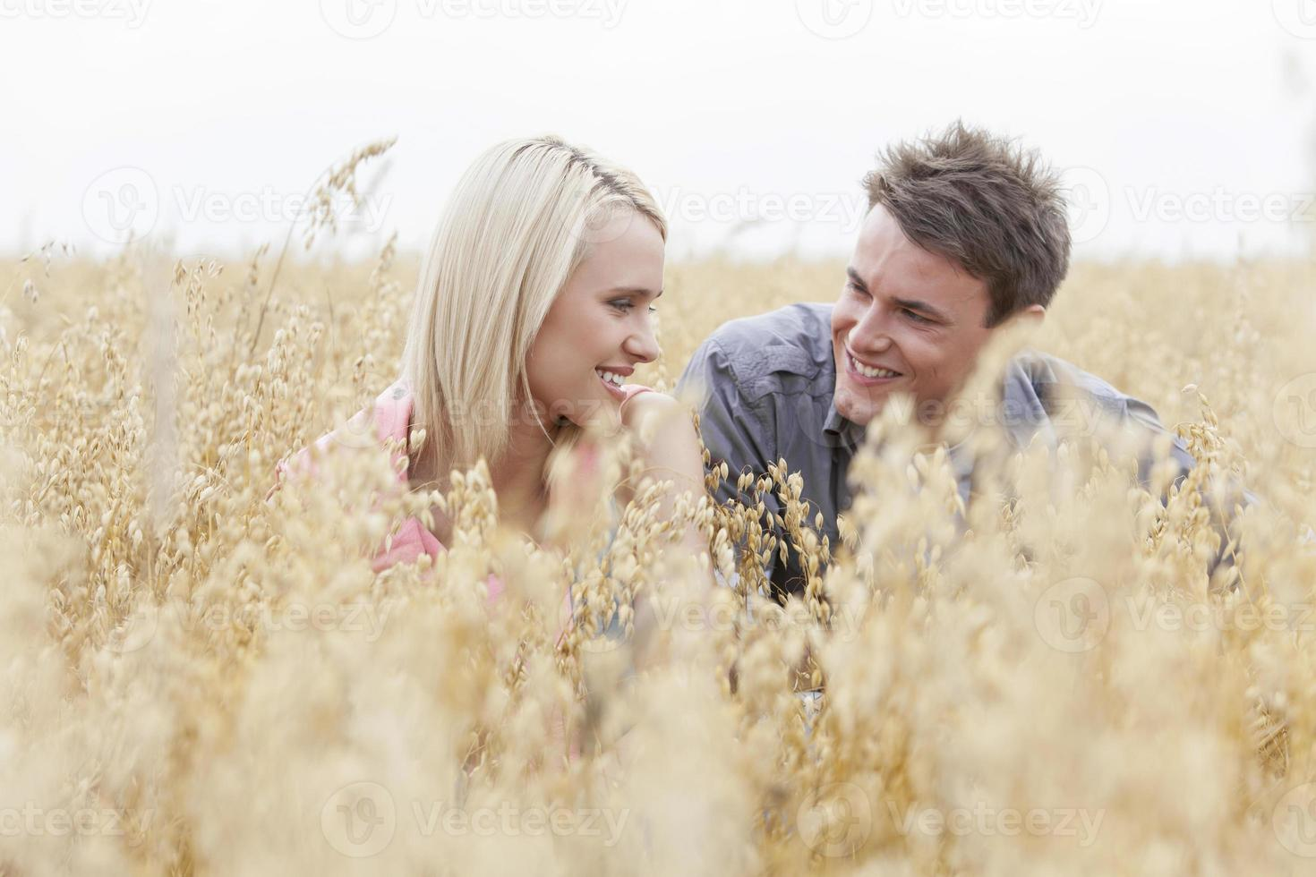 Happy man looking at woman while relaxing amidst field photo
