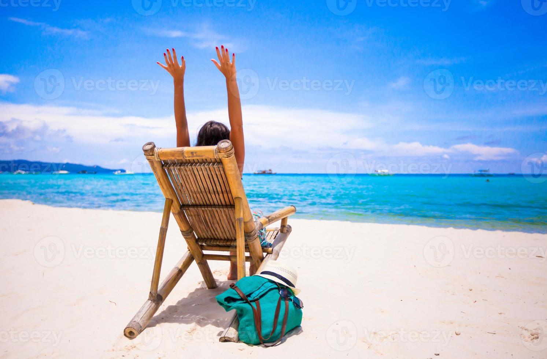 mujer joven relajante en silla de madera playa en vacaciones tropicales foto