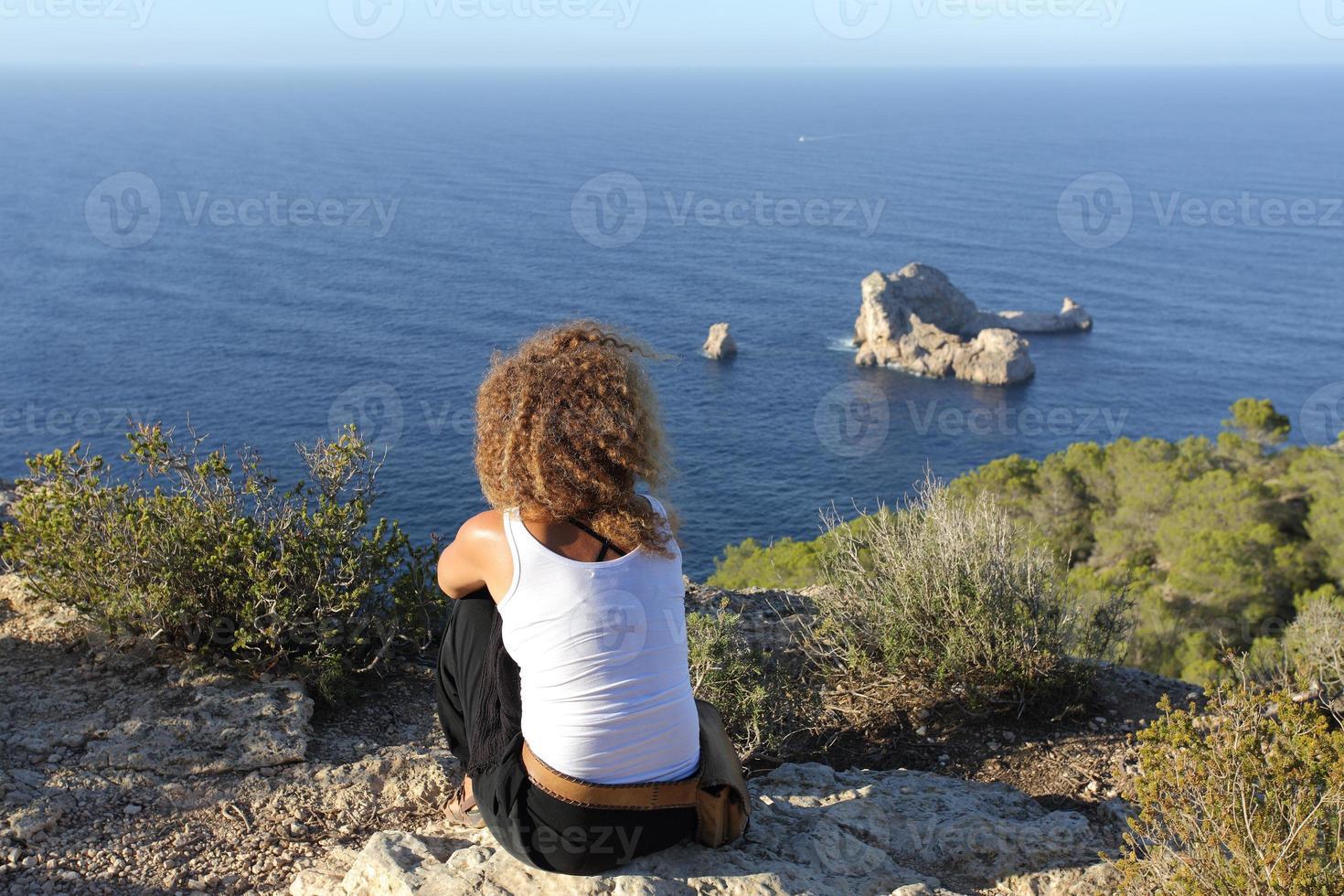 Mujer pensativa relajante en un acantilado en la isla de Ibiza foto