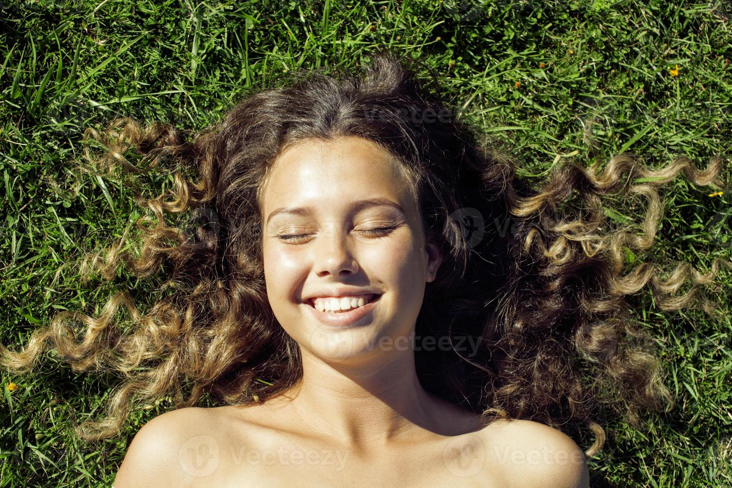 young cute summer girl on grass outside relaxing smiling photo