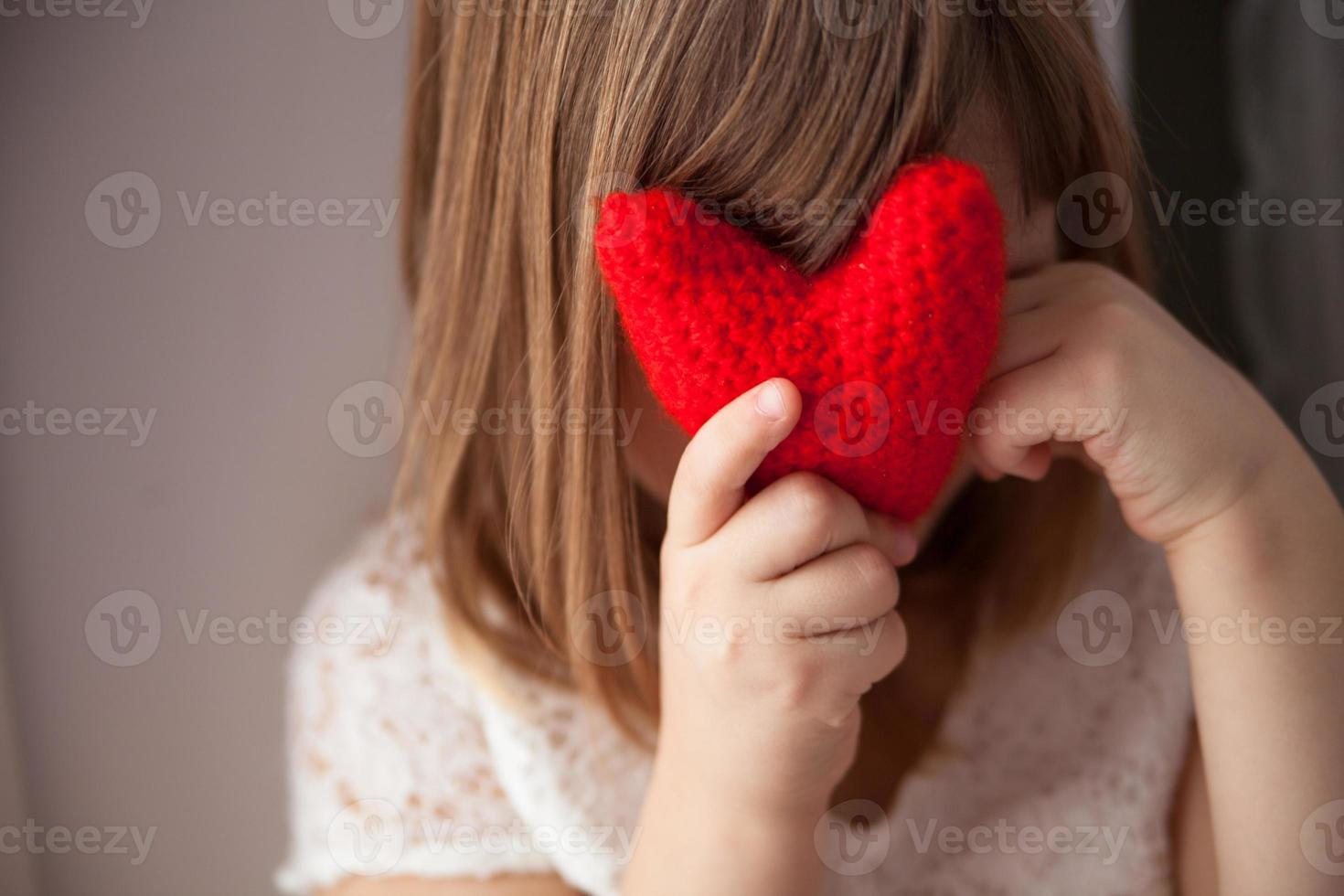 Girl hiding behind a knitted red heart, Valentine's Day, photo