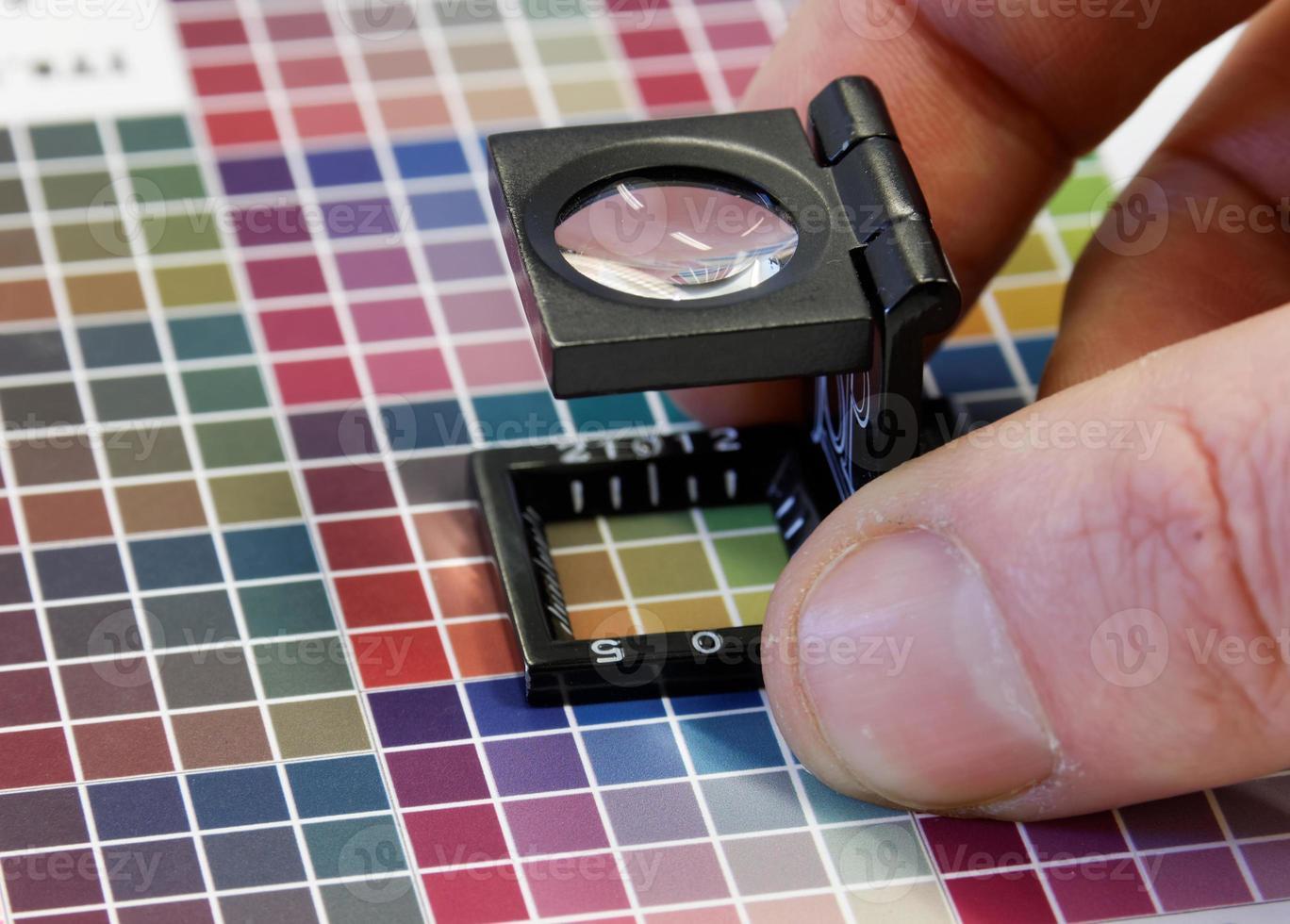 Primer plano de una lupa en una impresión de prueba colorida foto