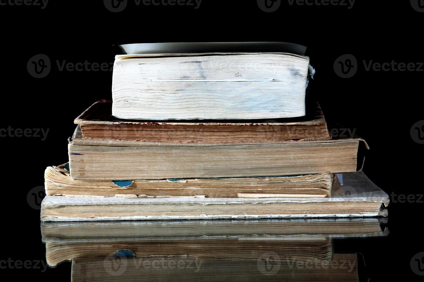 Stack of old books with vintage pages reflected photo