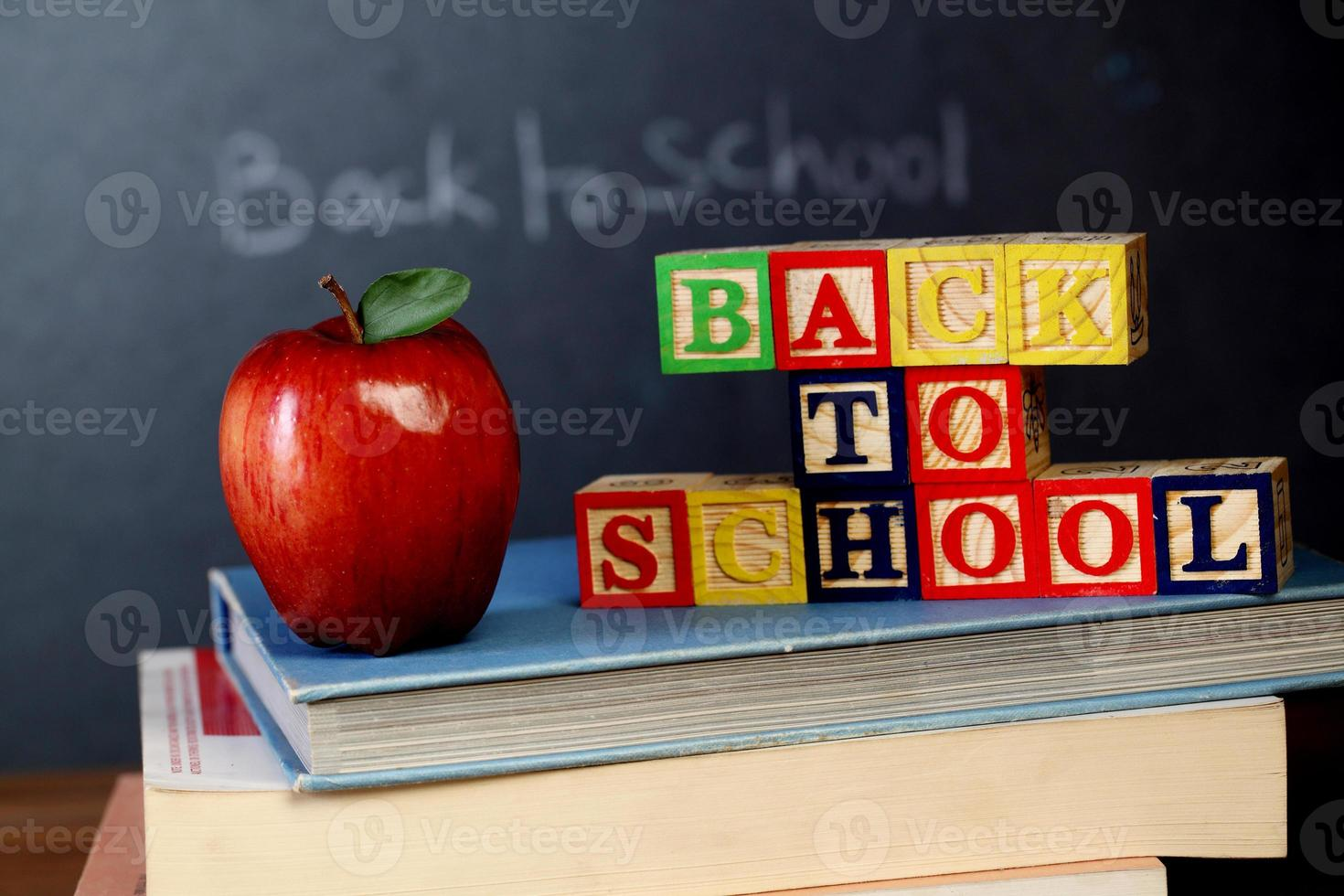 ABC blocks and apple against black board photo