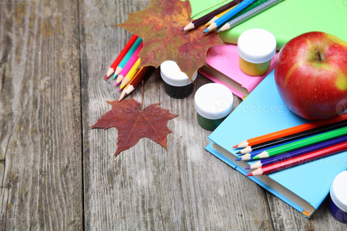libros, lápices y hojas de arce foto