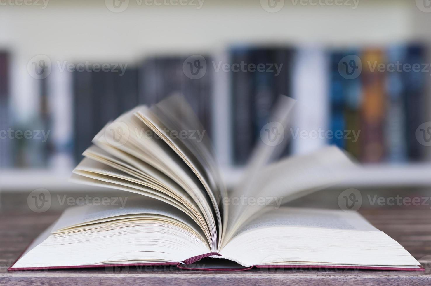 Opened book in front of bookcase photo