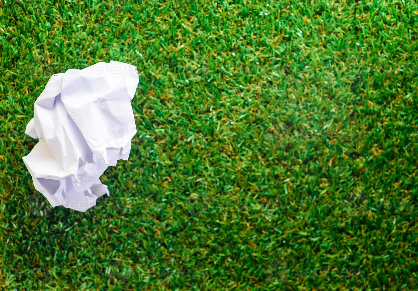 Crumpled paper on Green grass background photo