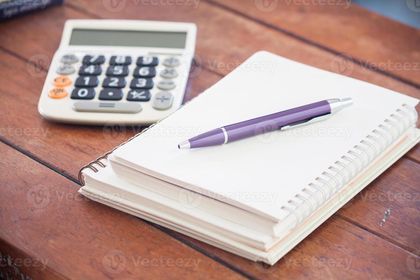 caderno em branco com caneta na mesa de madeira foto