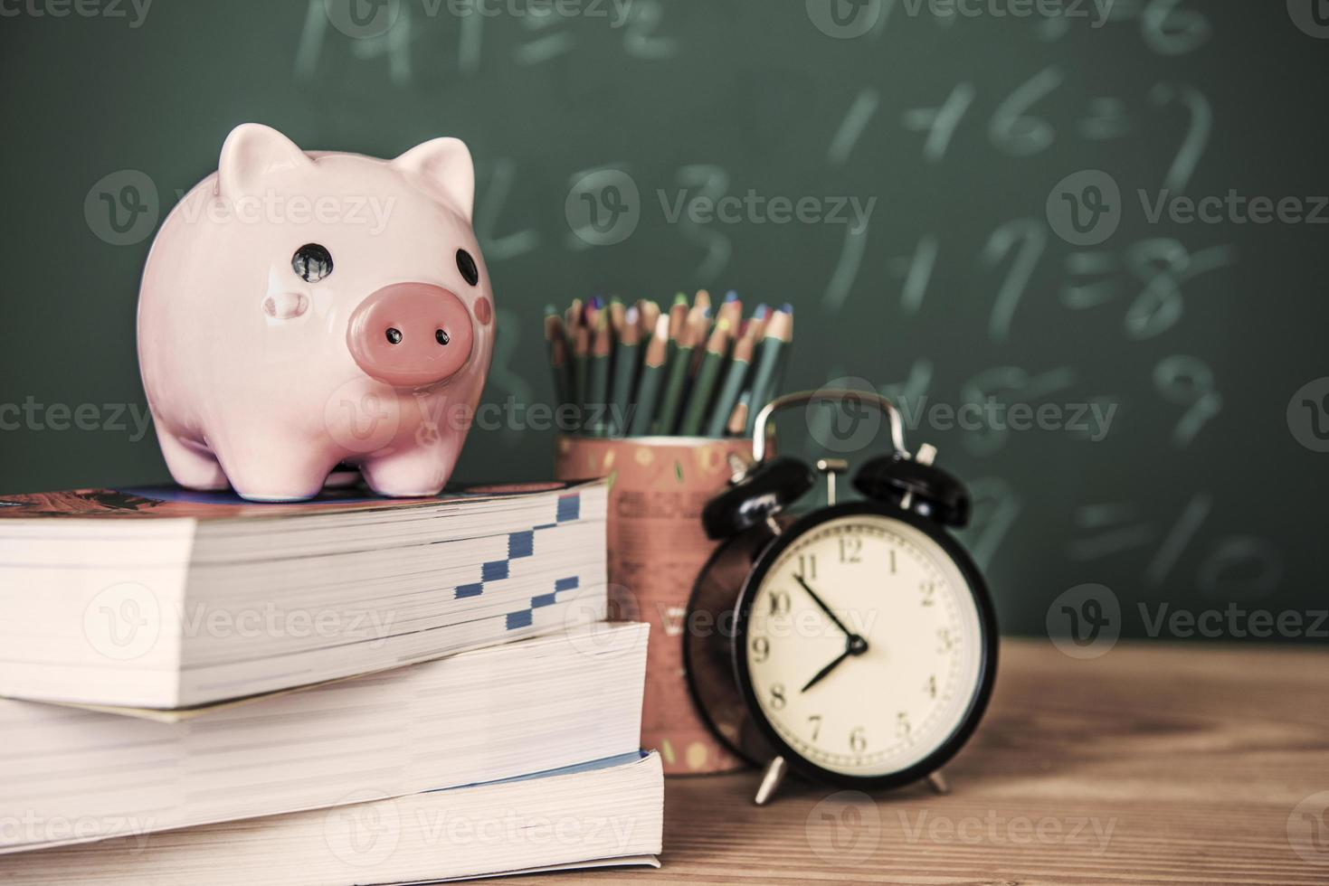Pig bank and a clock on a green background photo