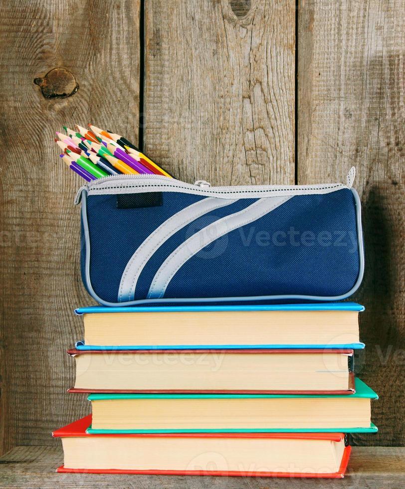 Libros y herramientas escolares en un estante de madera. foto