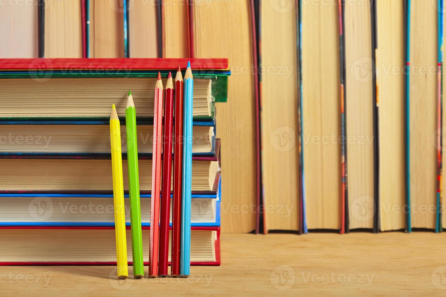 Pile of books and colored pencils on a wooden surface. photo
