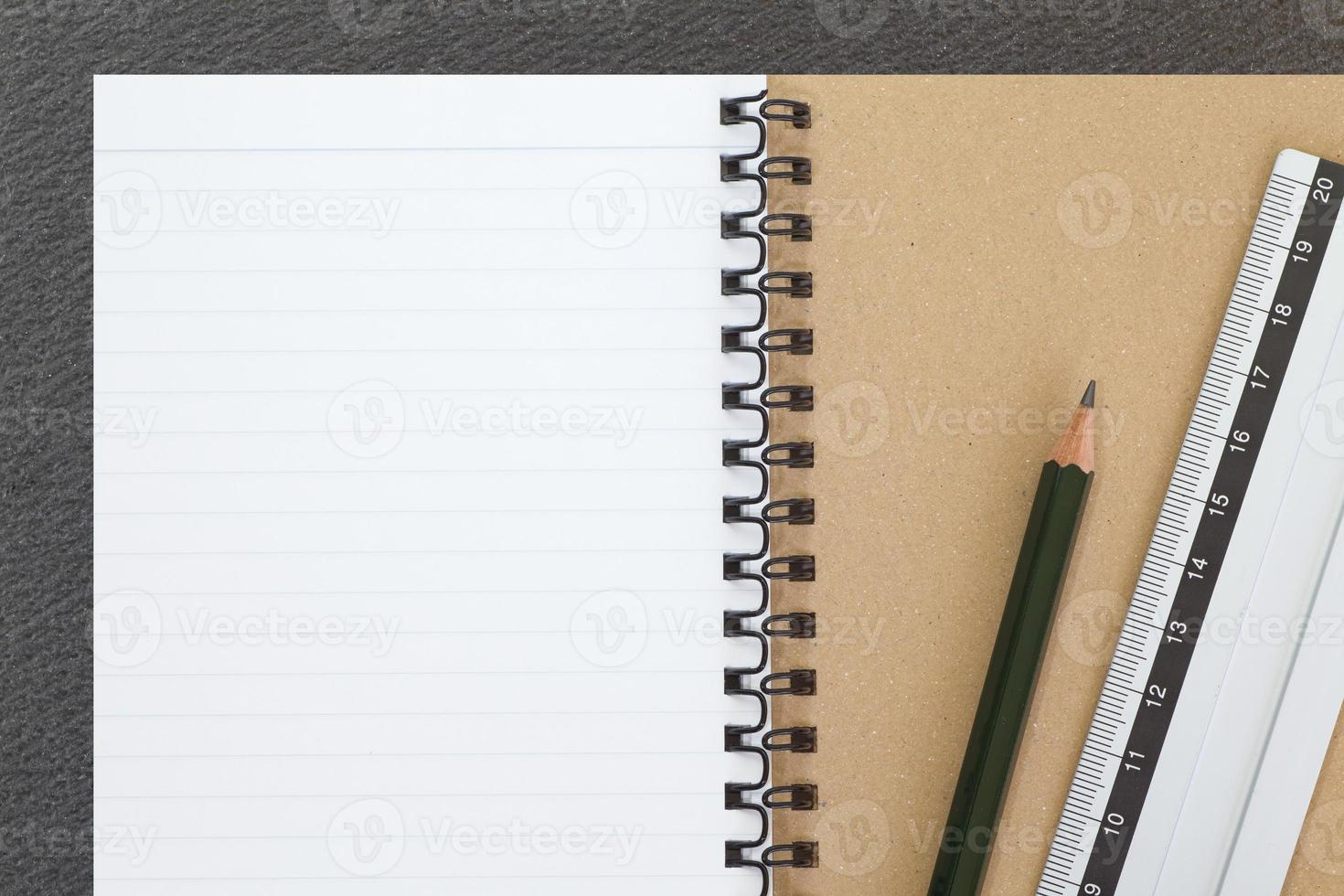 Open notebook and pencil on black table background photo