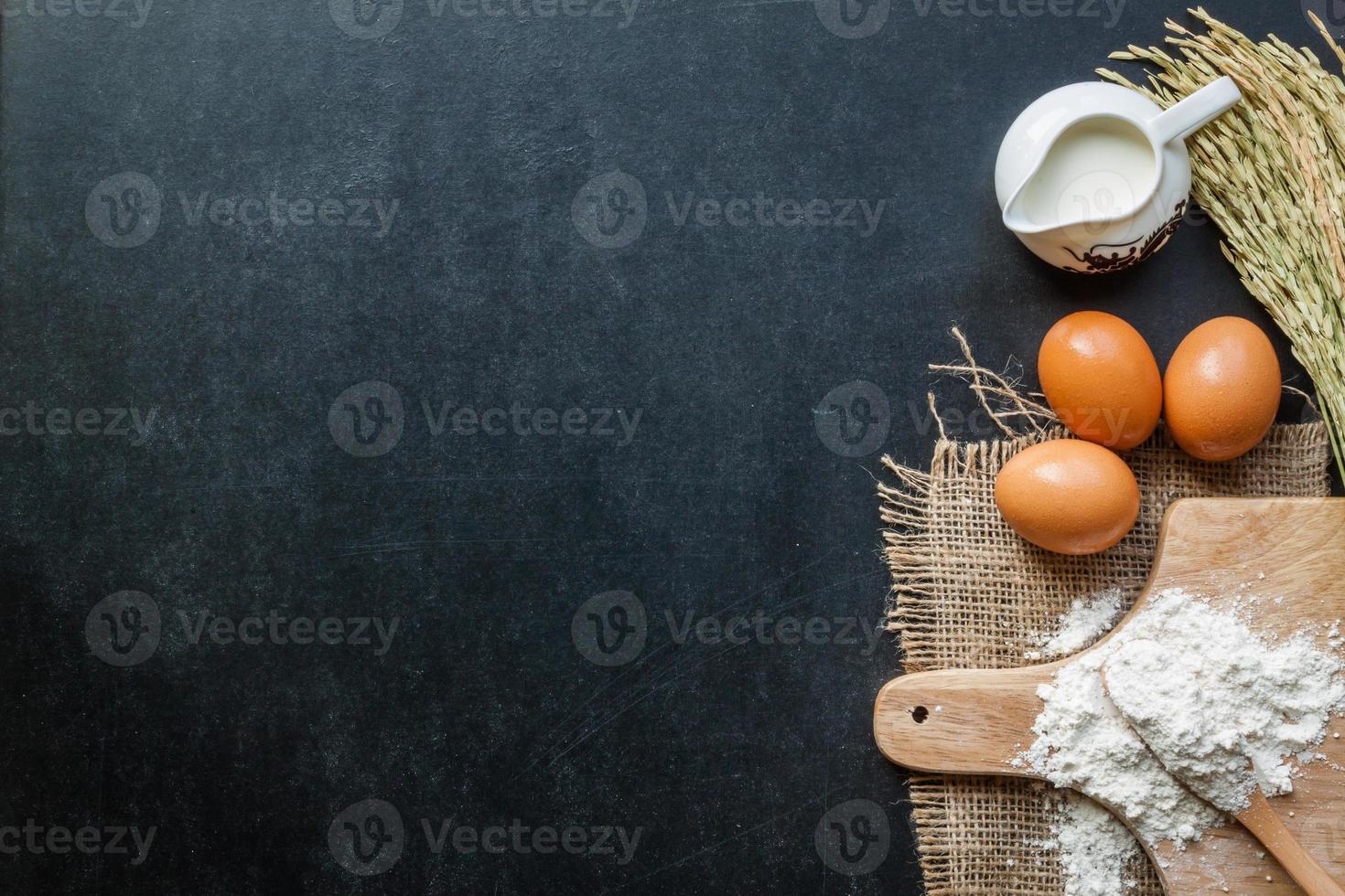 Leche en polvo para hornear y huevos en pizarra para el fondo foto