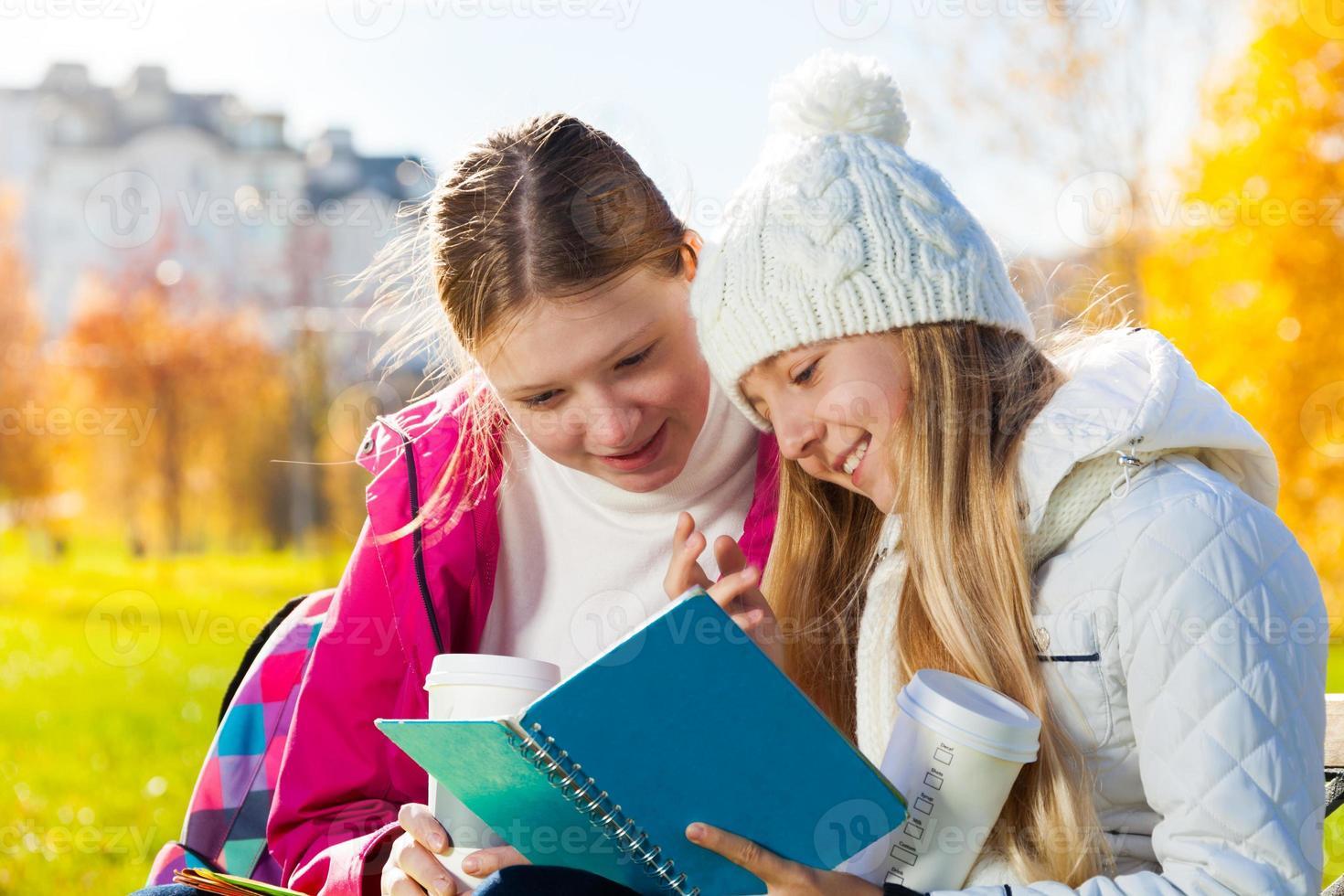 chicas hablando mirando al libro de texto foto