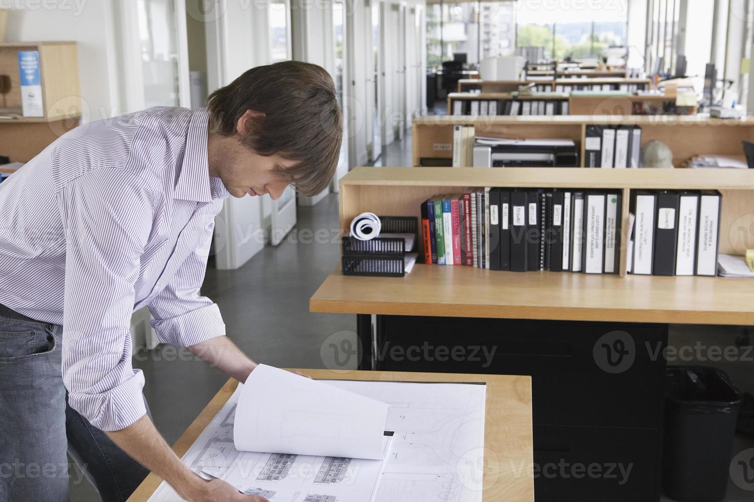 hombre estudiando planos en oficina foto
