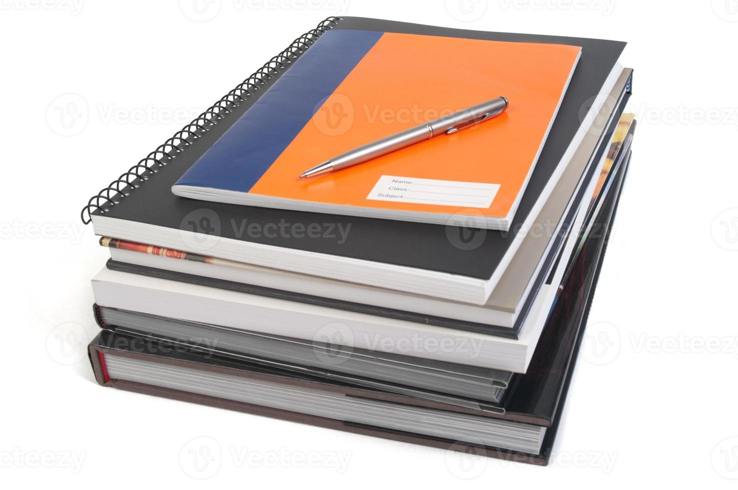 Reference books, notebooks and pen photo