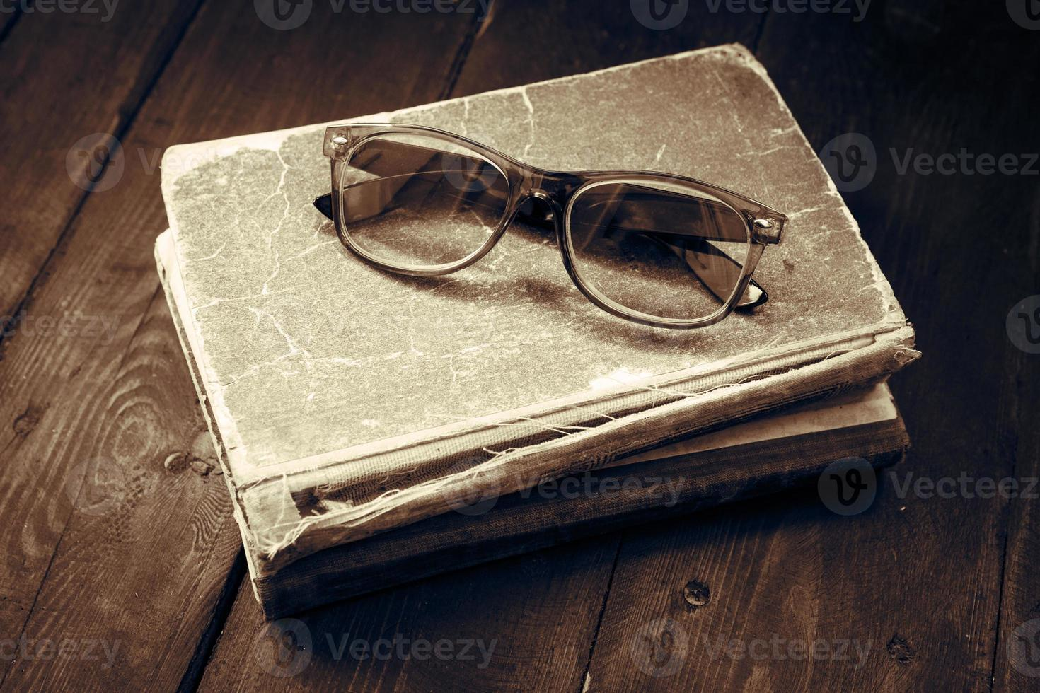 Vintage reading glasses on the books stack photo