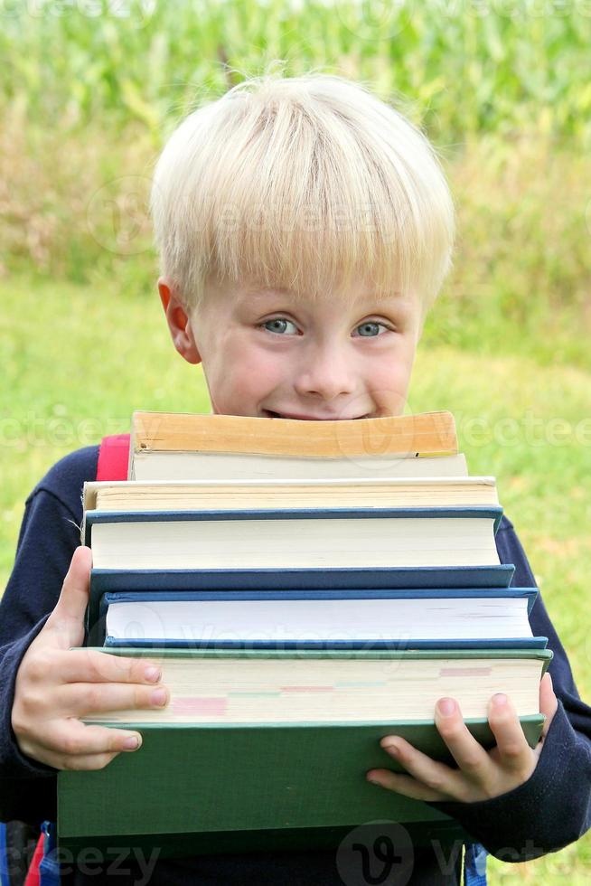 Little Child Carrying Lots of Big Heavy School Books photo
