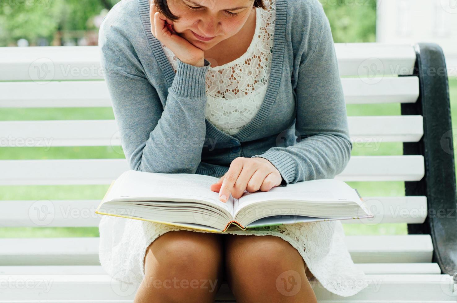 Young woman reads on a bench in park photo