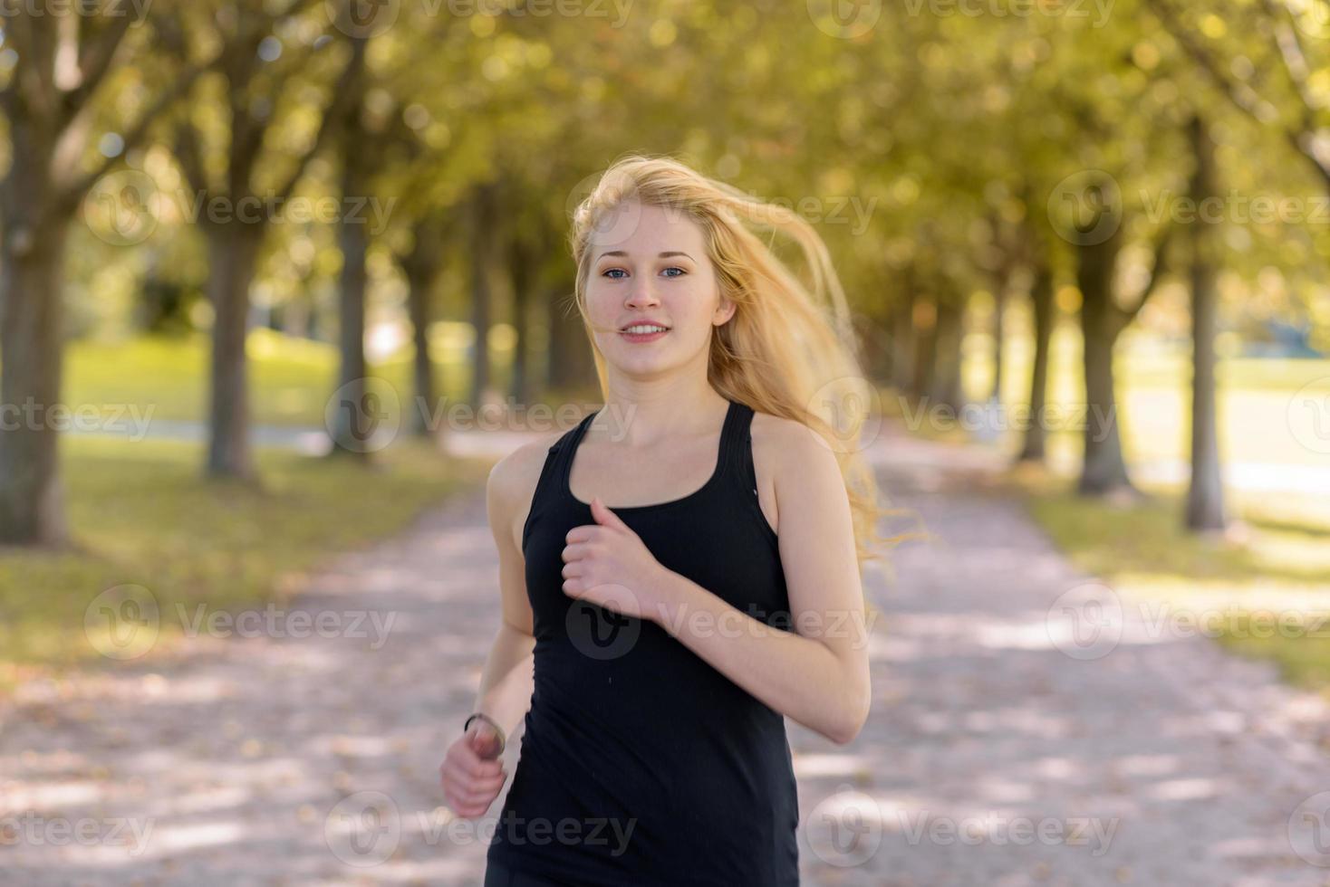 joven mujer rubia corriendo en un camino con grandes árboles foto