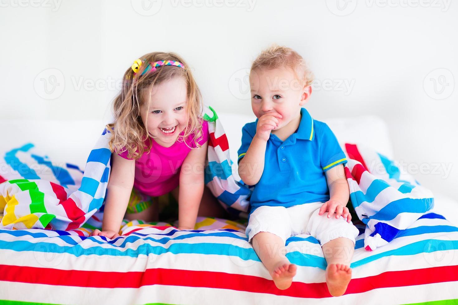 dulces niños durmiendo bajo una manta colorida foto