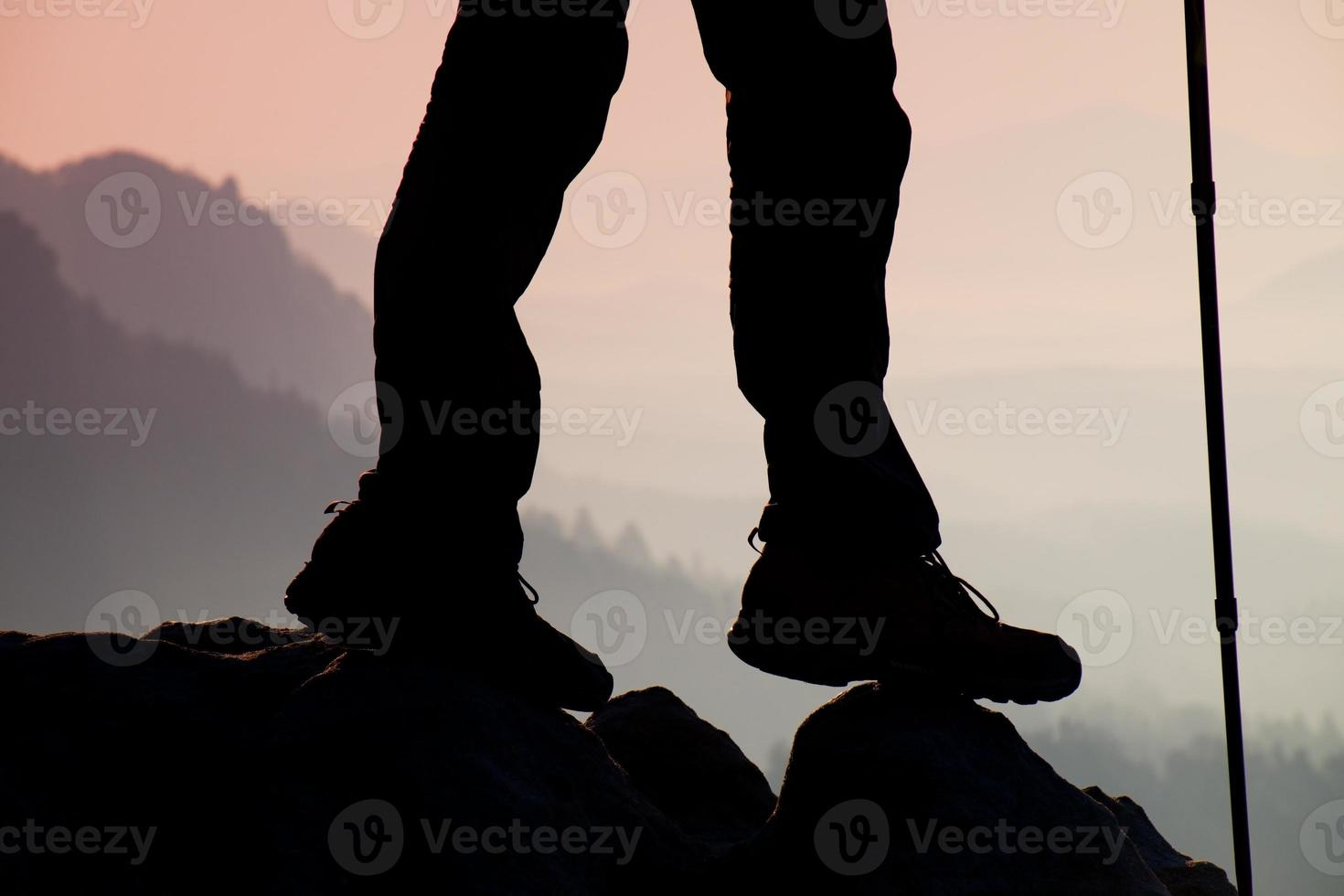 Woman hiker legs in tourist boots stand on mountain rock photo