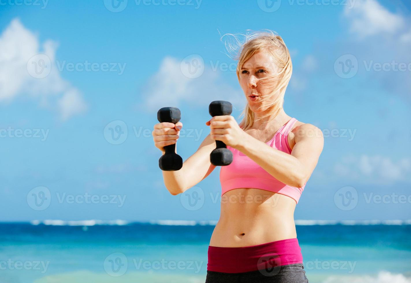 Fitness woman with barbells working out photo