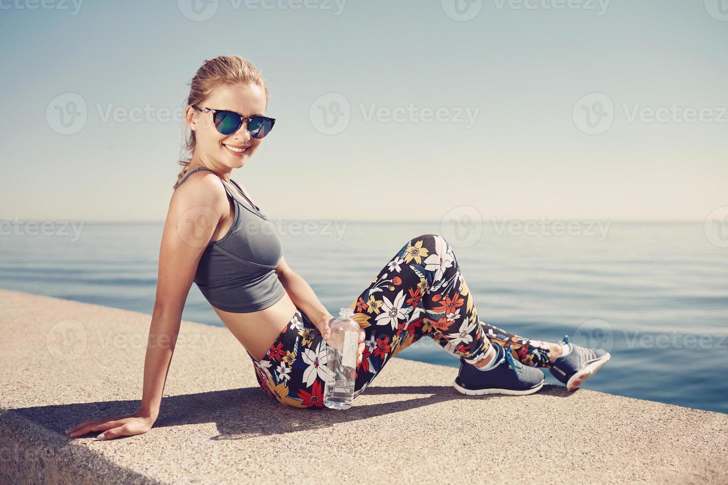 joven fitness mujer rubia sostenga la botella de agua después del ajuste foto