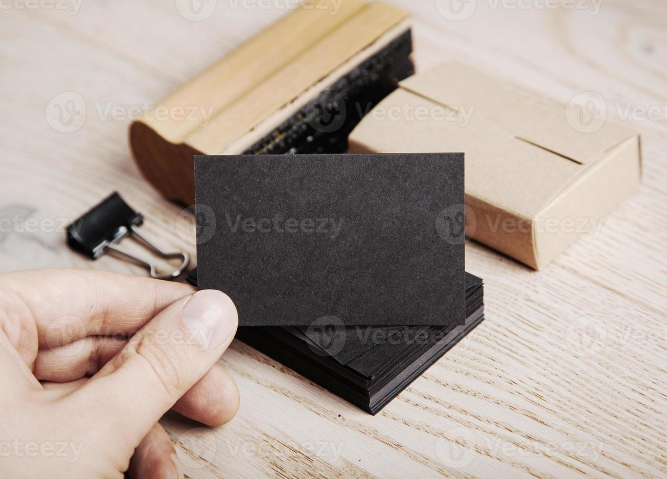 Man holding black business card. Set of blank office elements photo