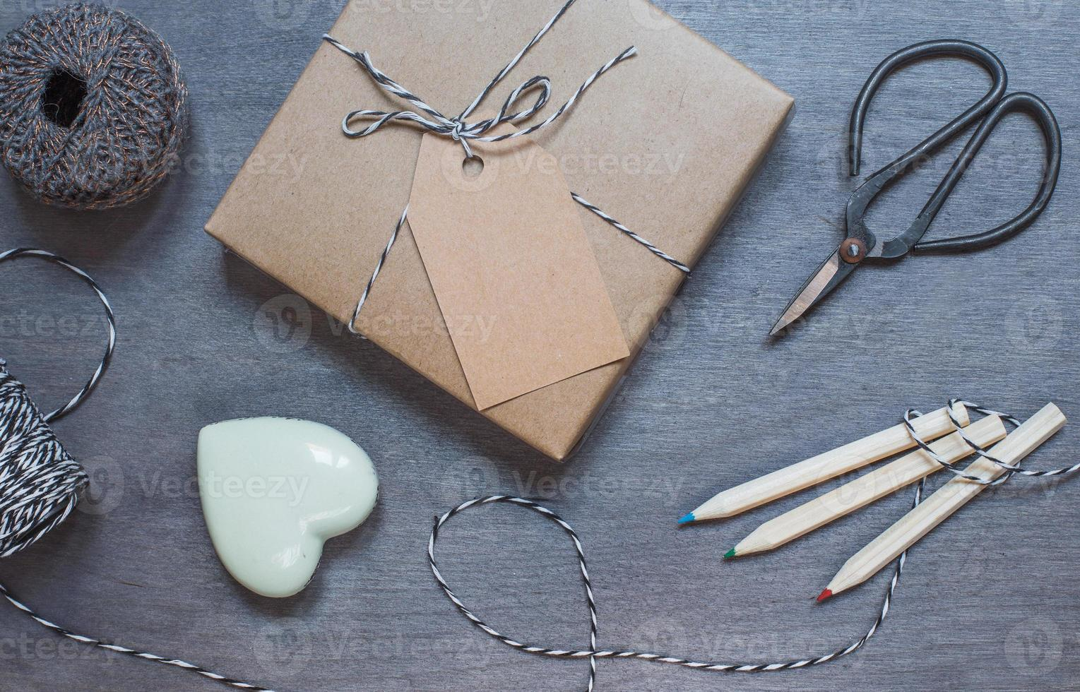 Gift box with ceramic heart, pencils and old scissors photo