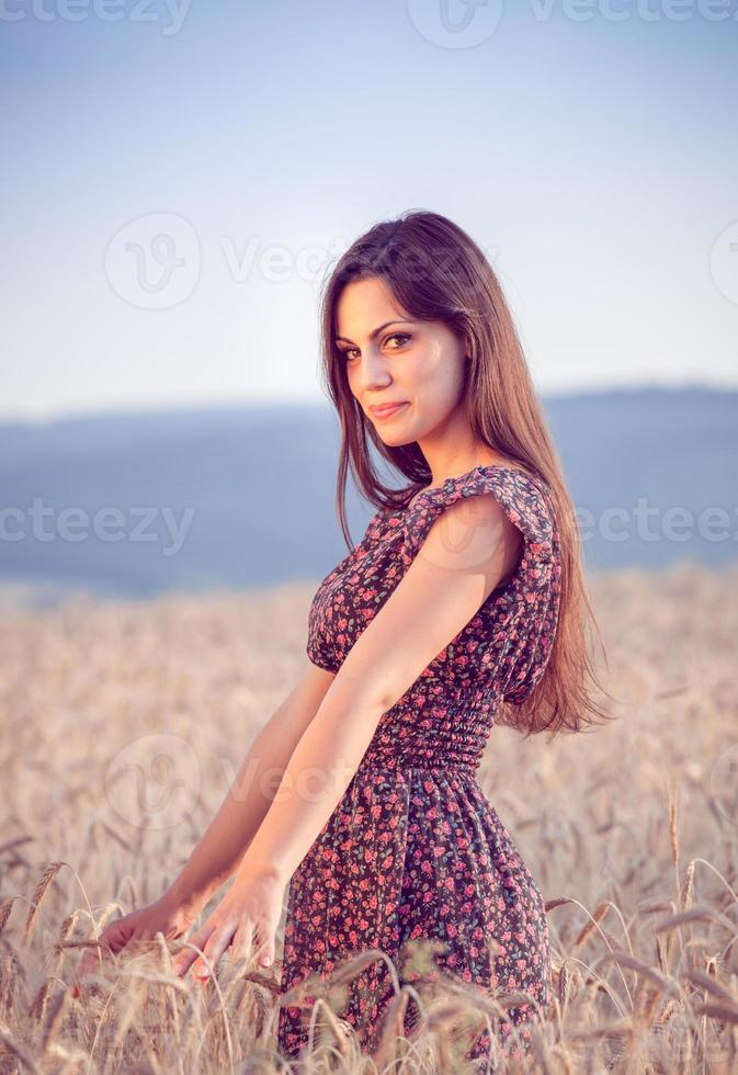 hermosa chica en campo de trigo al atardecer foto