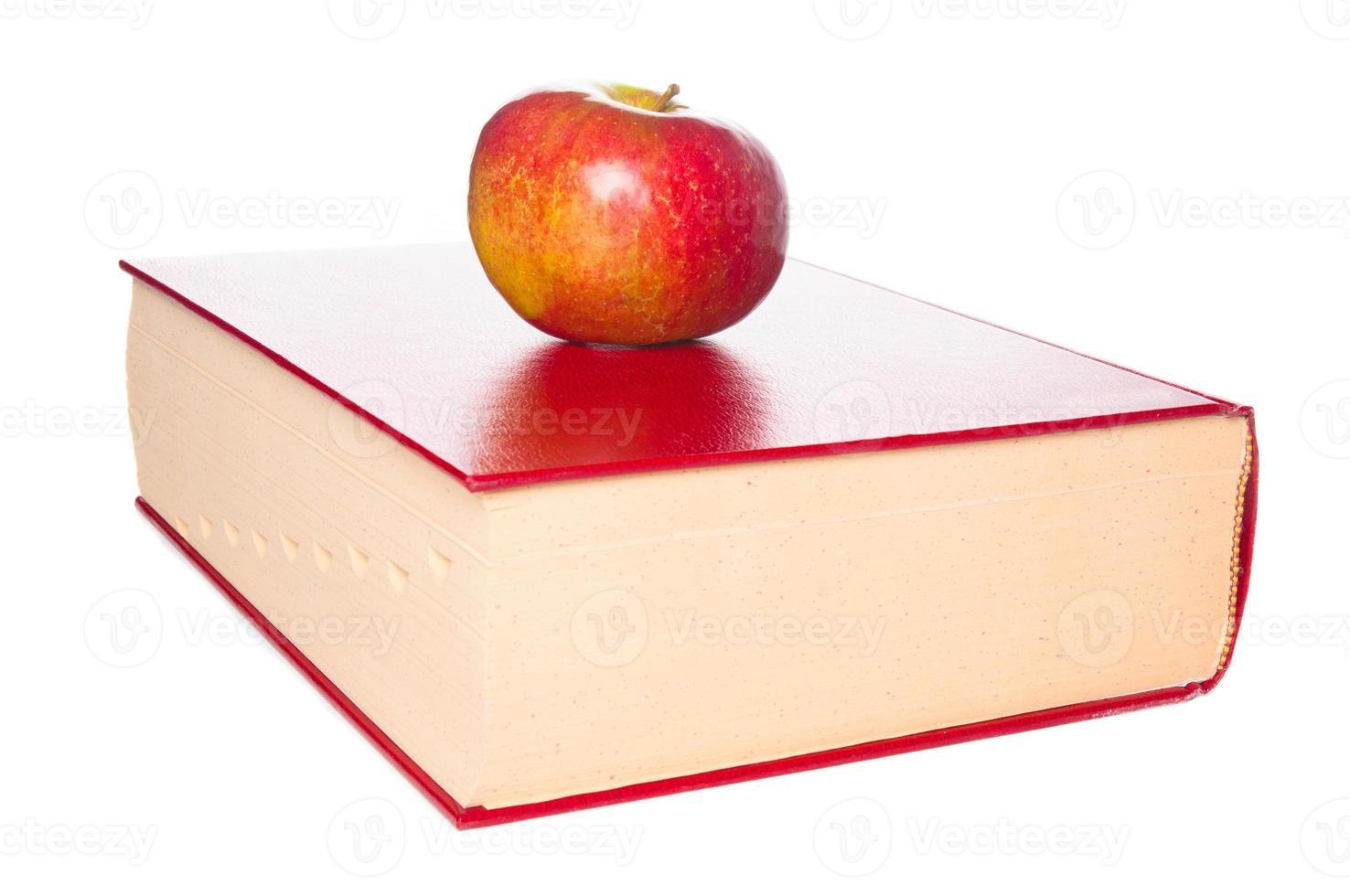 Diccionario y primer plano de manzana sobre fondo blanco. foto