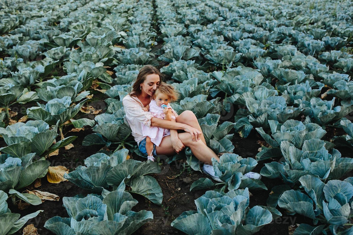 madre e hija en el campo con repollo foto