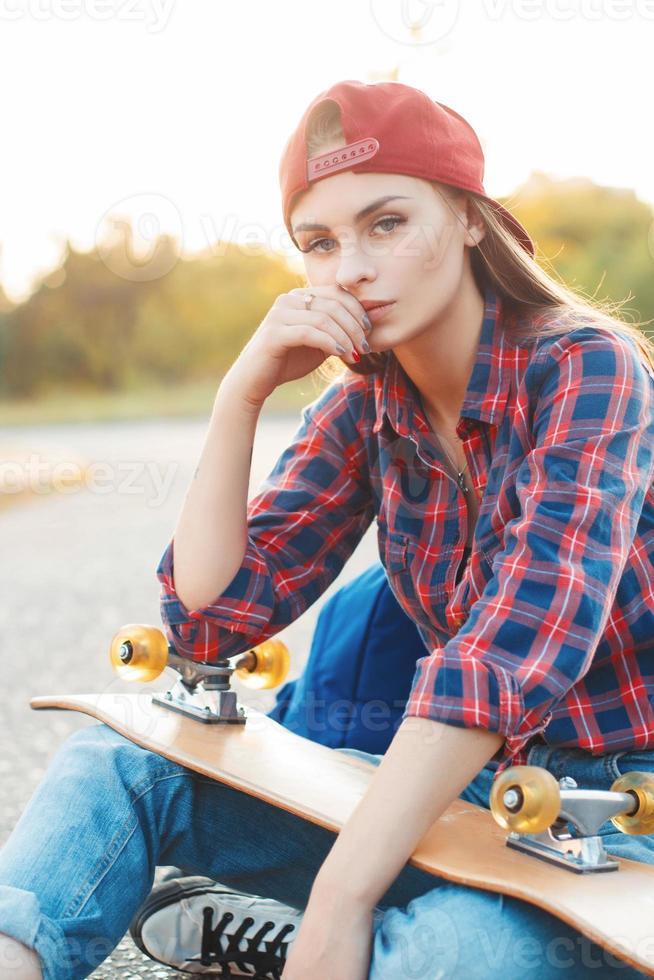 estilo de vida de moda, hermosa mujer joven con patineta foto