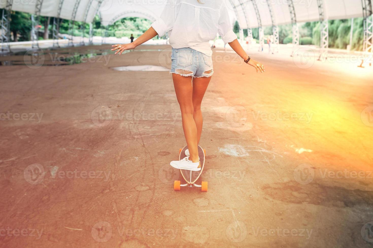 estilo de vida de moda, hermosa mujer joven con longboard foto