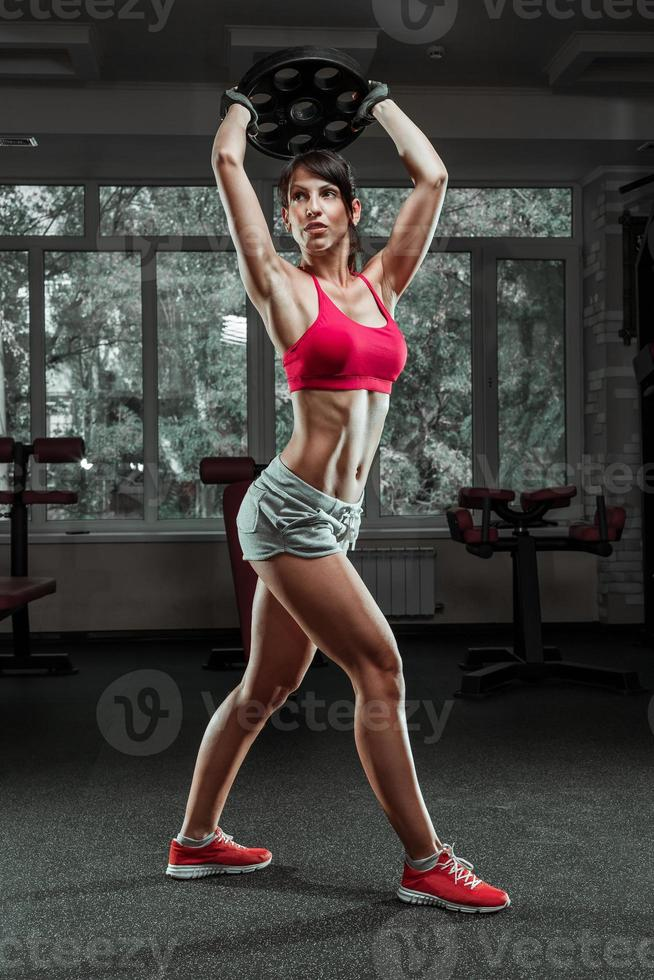 Fitness woman swinging kettle bell at gym photo