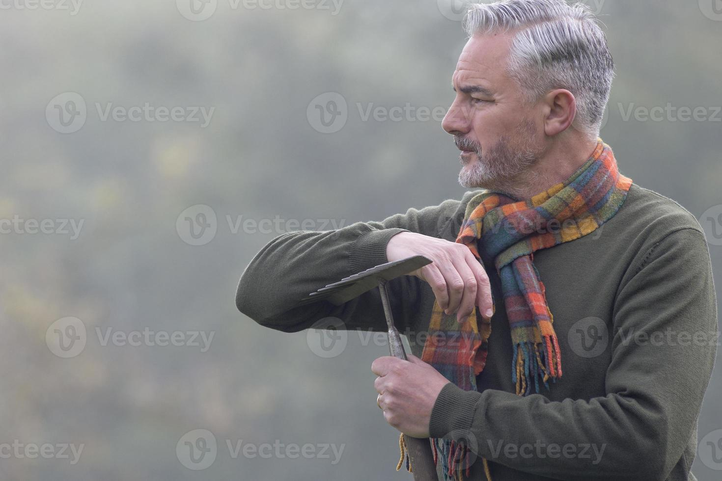 Man with rake looking into the fog photo