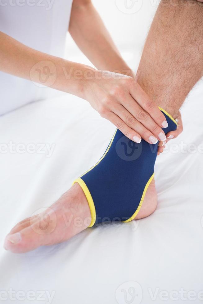Doctor examining her patient foot photo