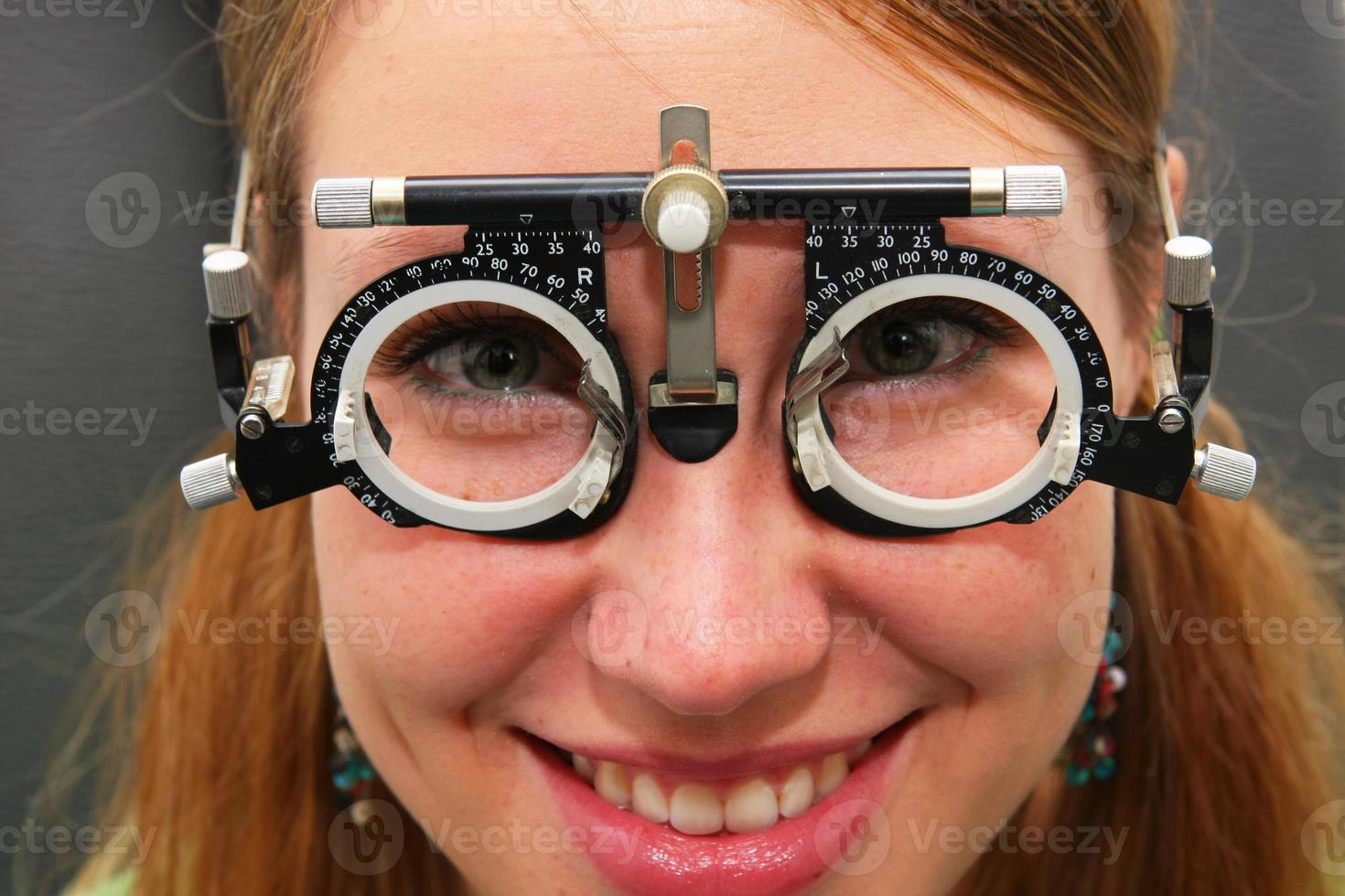 Young girl at the optometrist checking her vision photo