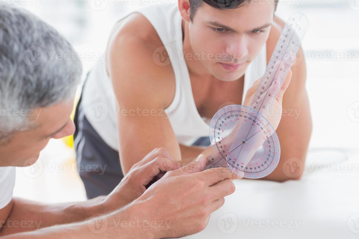 Doctor measuring wrist with goniometer photo