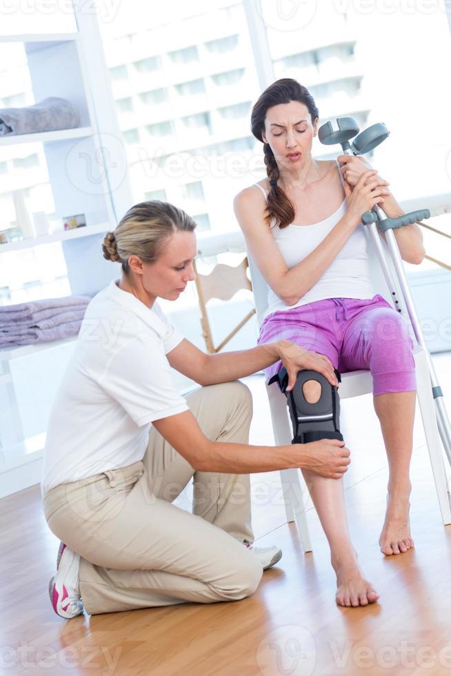 Doctor examining her patients knee photo