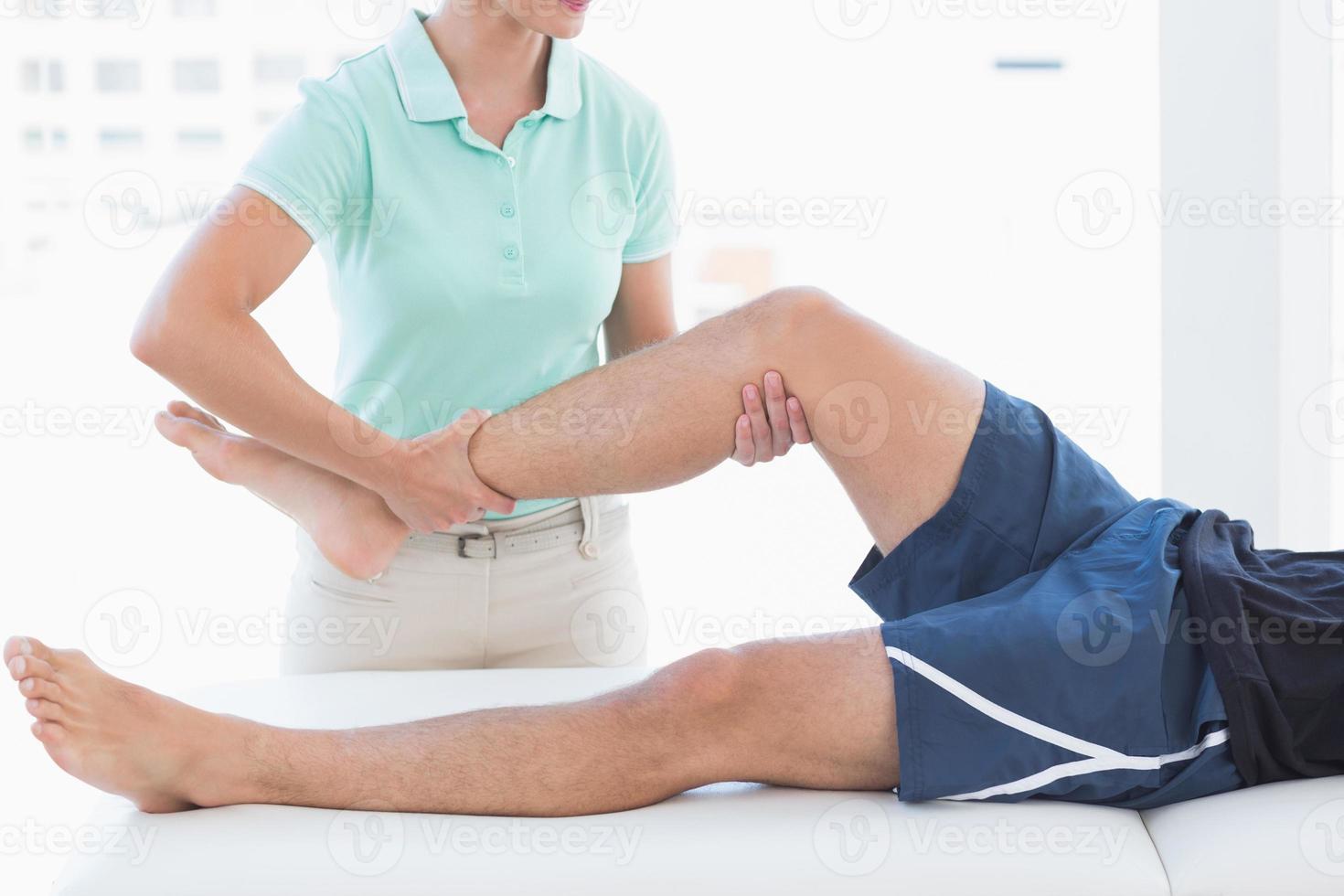 médico examinando la pierna del hombre foto