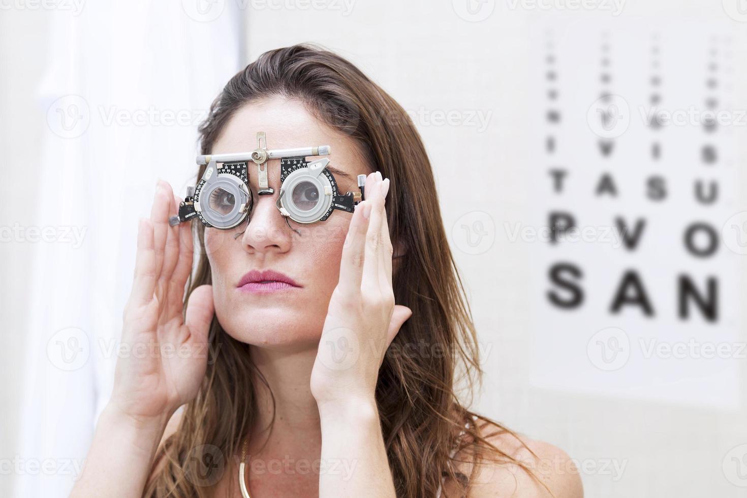 hermosa mujer prueba nuevas lentes auxiliares con foróptero foto