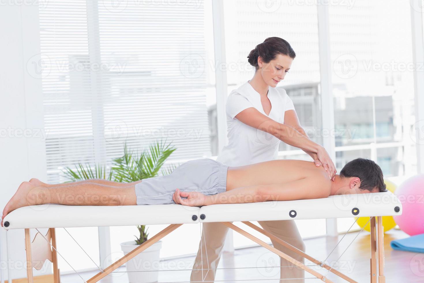 fisioterapeuta haciendo masaje de cuello foto