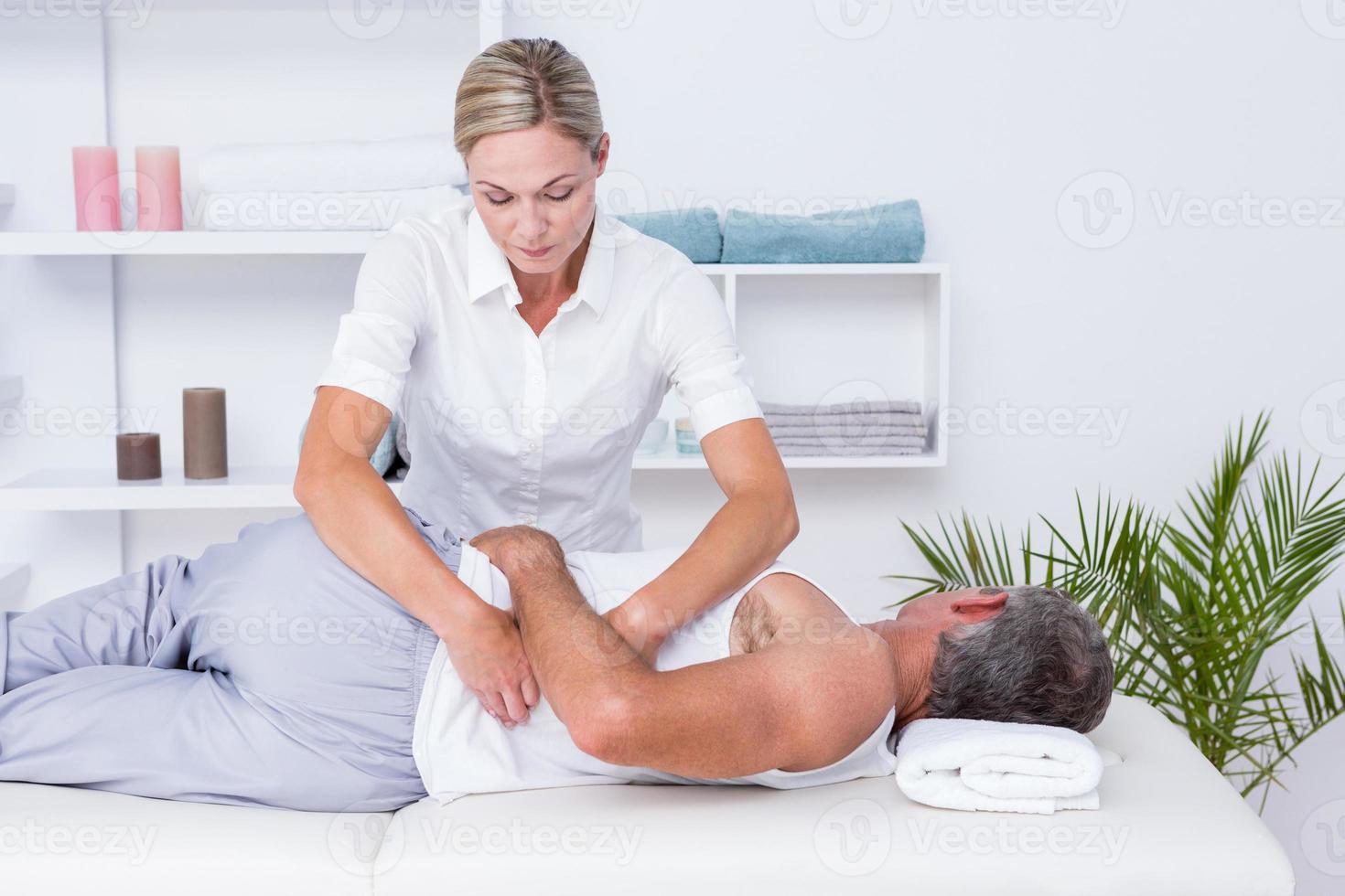 fisioterapeuta haciendo masaje de hombro a su paciente foto