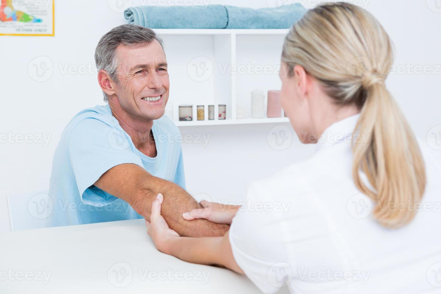 doctor haciendo masaje de brazo foto