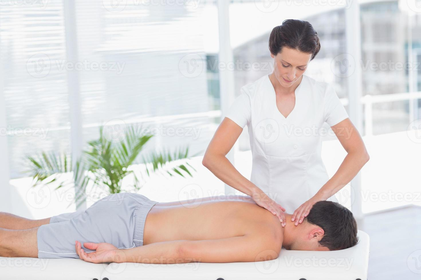 fisioterapeuta haciendo masaje de cuello a su paciente foto
