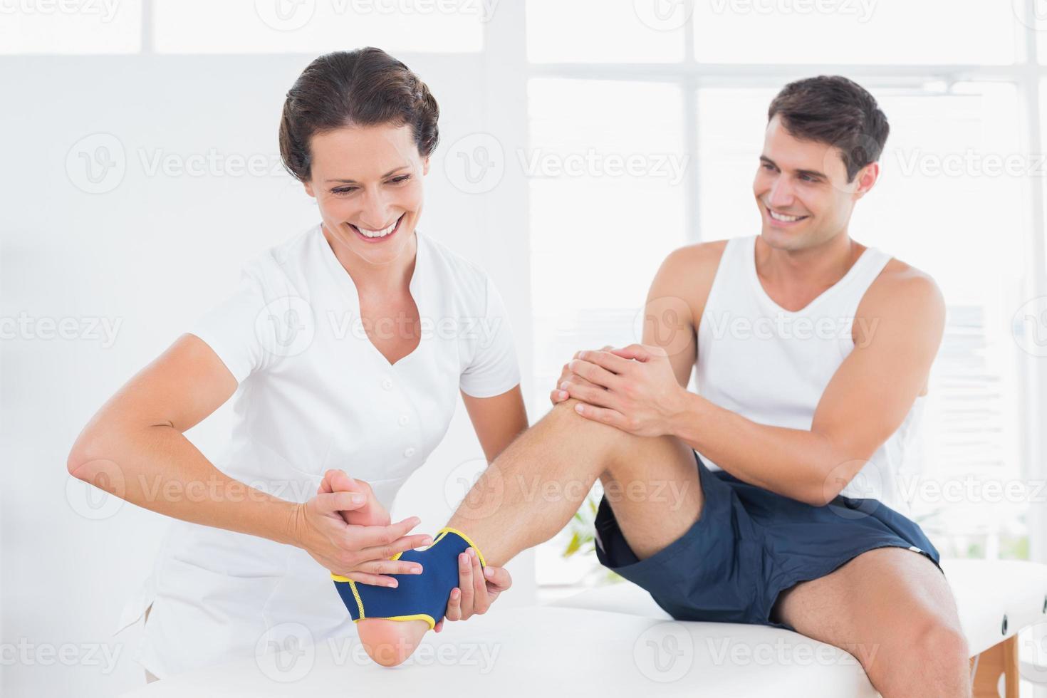 médico examinando su pie paciente foto