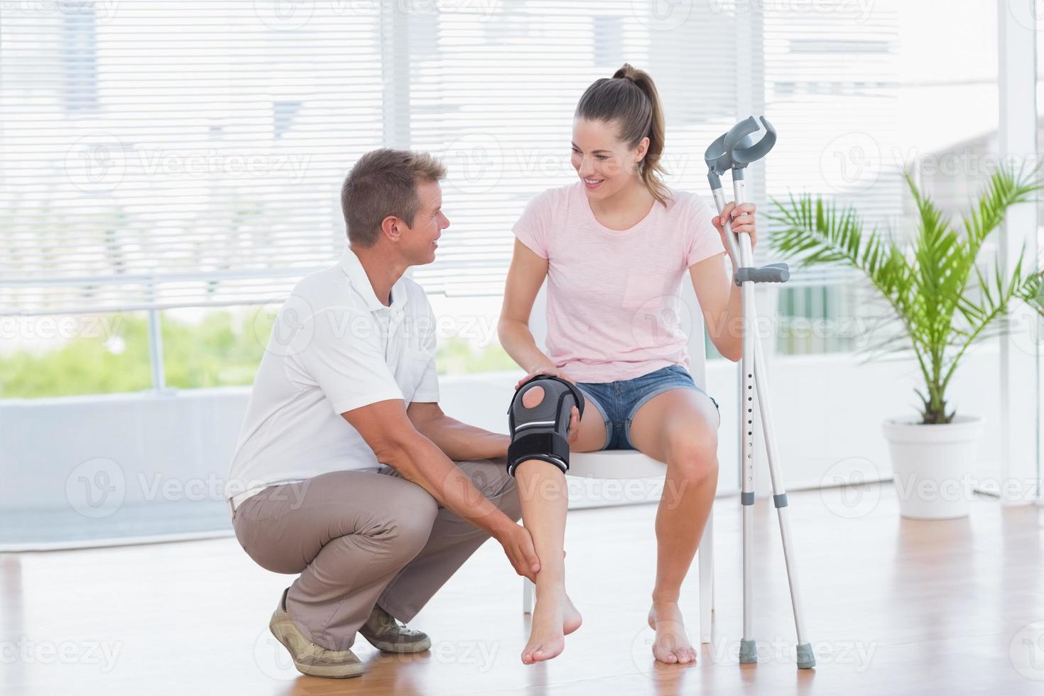 médico examinando su rodilla paciente foto